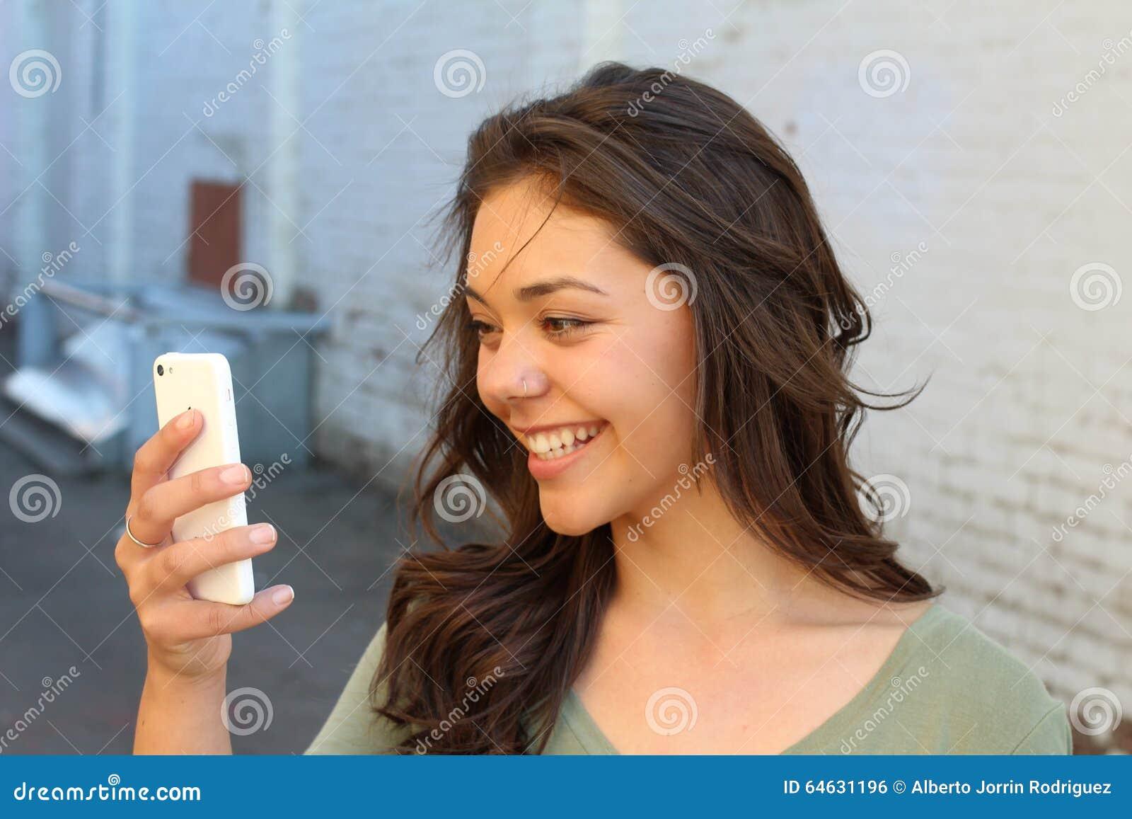 Jeune femme heureuse à l aide d un téléphone intelligent dans la rue avec un fond unfocused prenant un selfie ou employant Skype