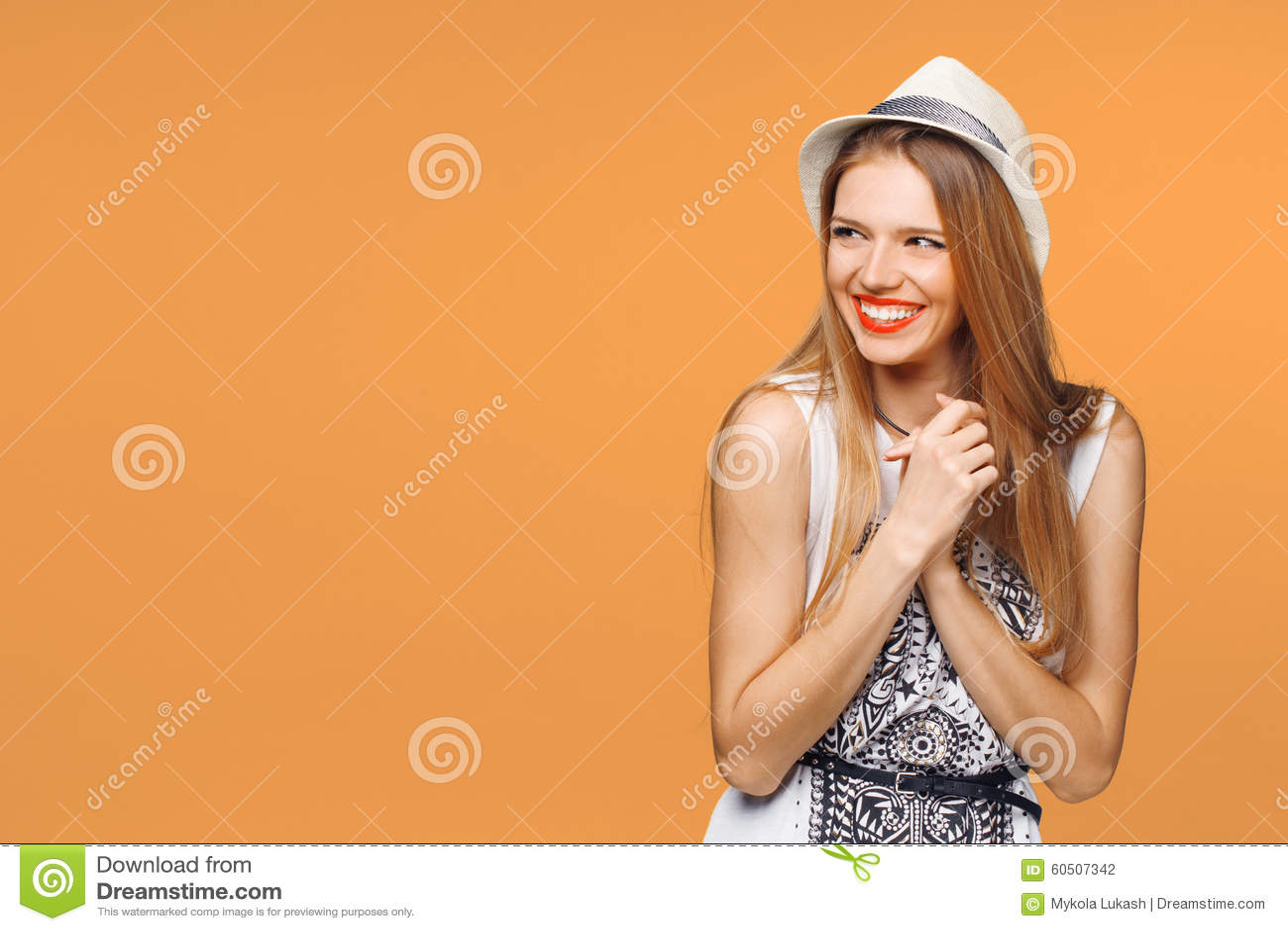 Jeune femme heureuse étonnée regardant en longueur dans l excitation D isolement au-dessus du fond orange