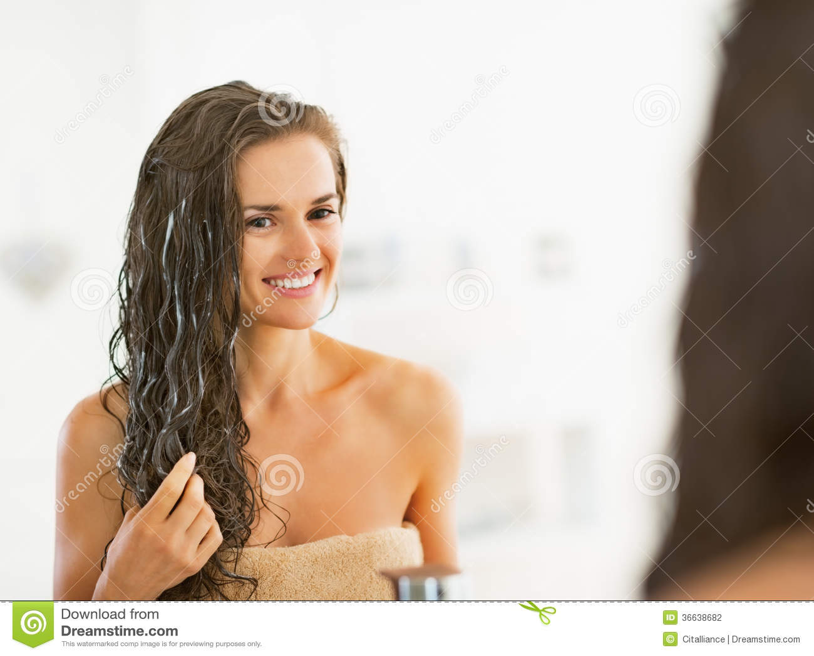 Jeune femme heureuse appliquant le masque de cheveux dans la salle de bains