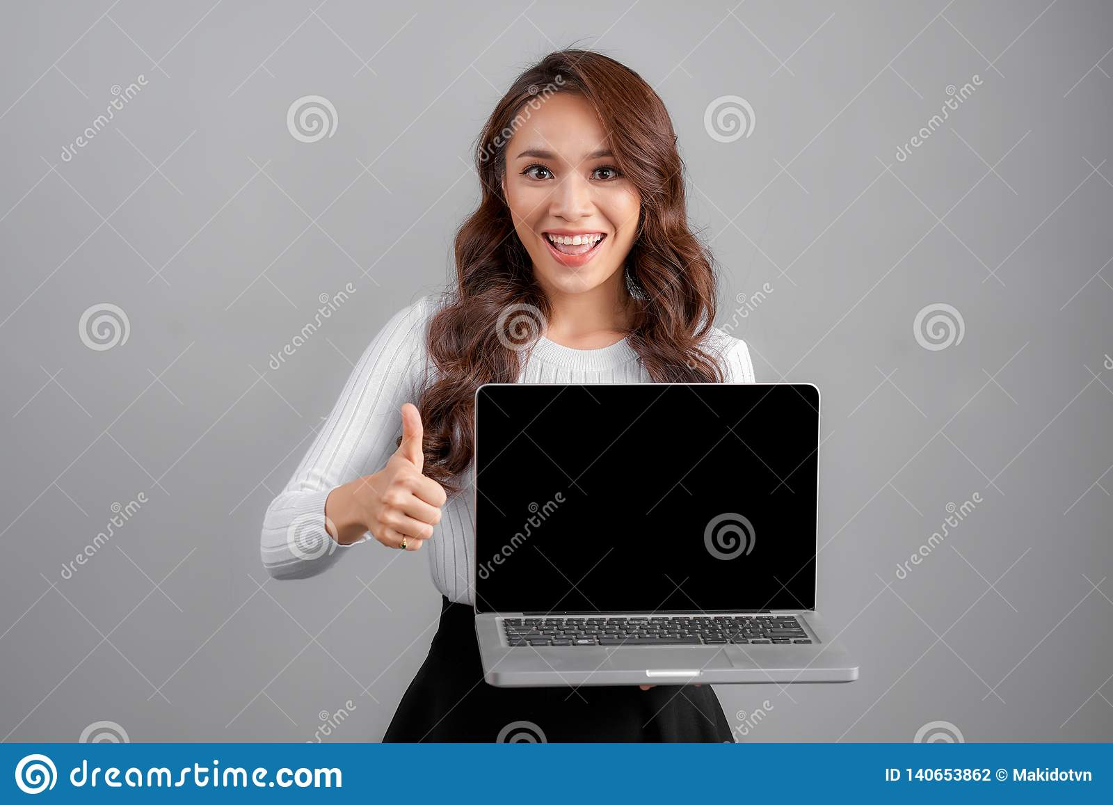 Jeune femme heureuse asiatique avec l ordinateur portable de carnet d isolement sur le fond gris