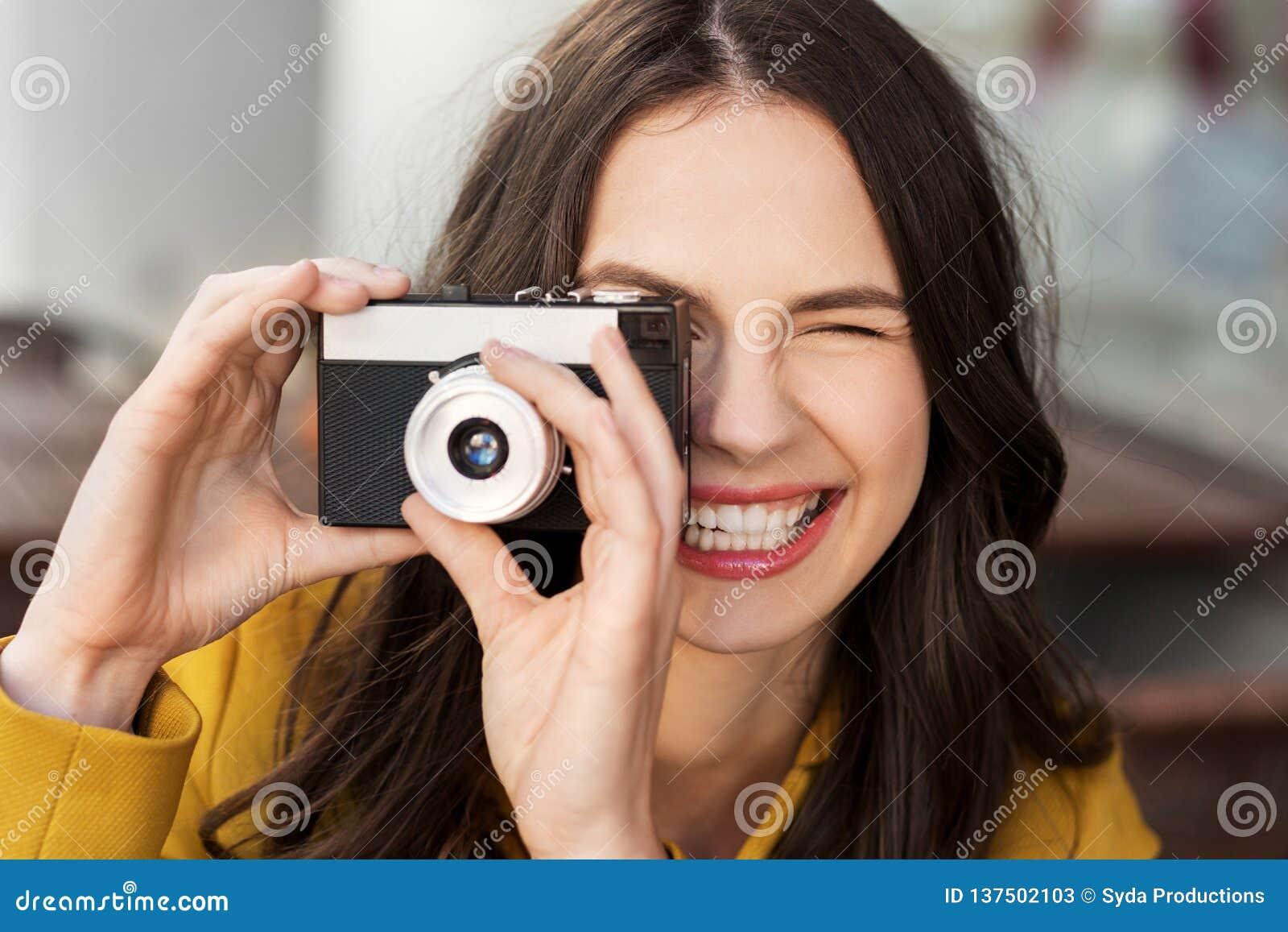 Jeune femme heureuse avec l appareil-photo de film dehors
