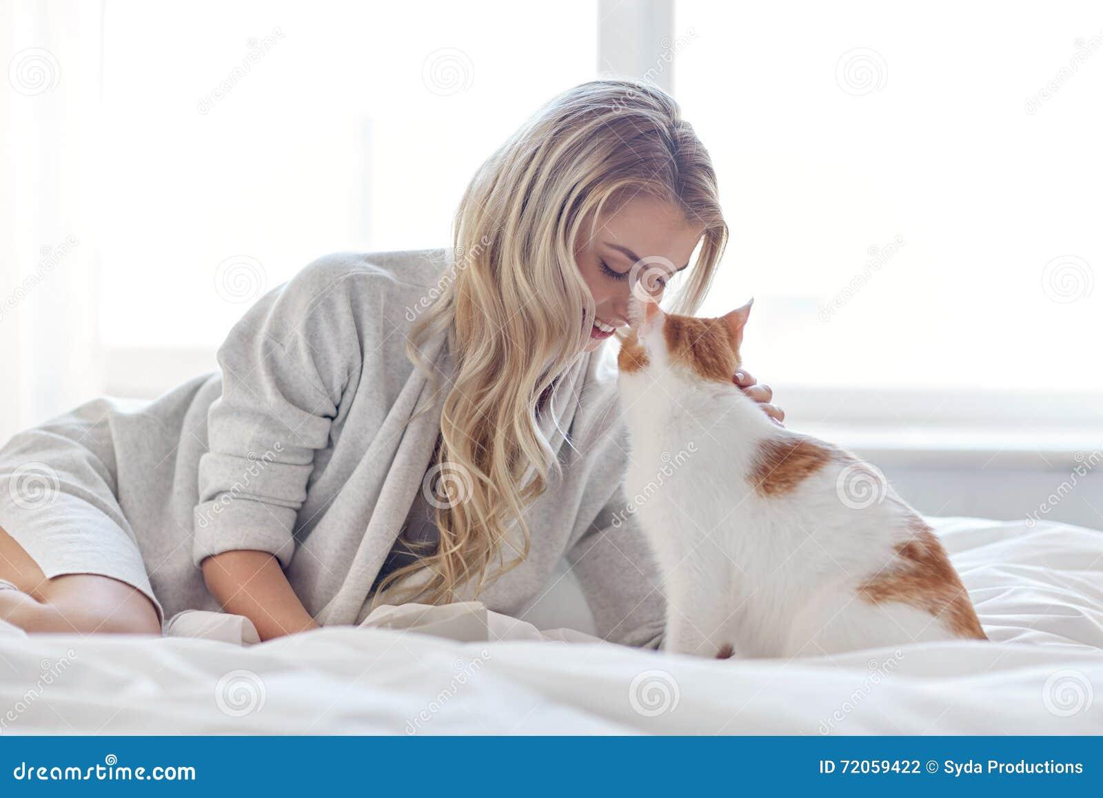jeune femme heureuse avec le chat dans le lit la maison photo stock image 72059422. Black Bedroom Furniture Sets. Home Design Ideas