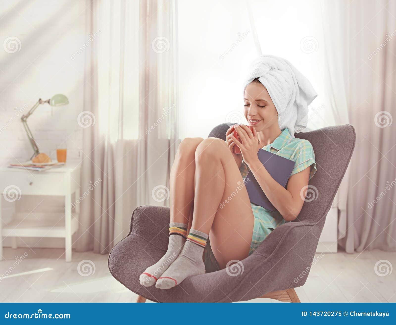 Jeune femme heureuse avec le livre et la tasse de café aromatique dans le fauteuil à la maison