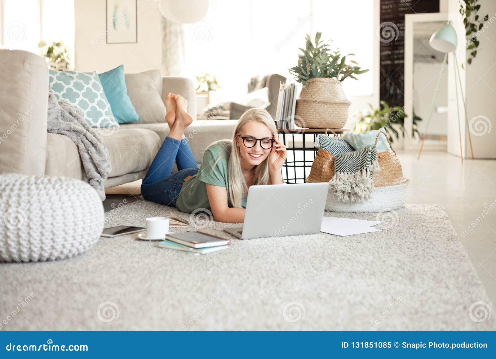 Jeune femme heureuse détendant à la maison et à l aide de l ordinateur portable
