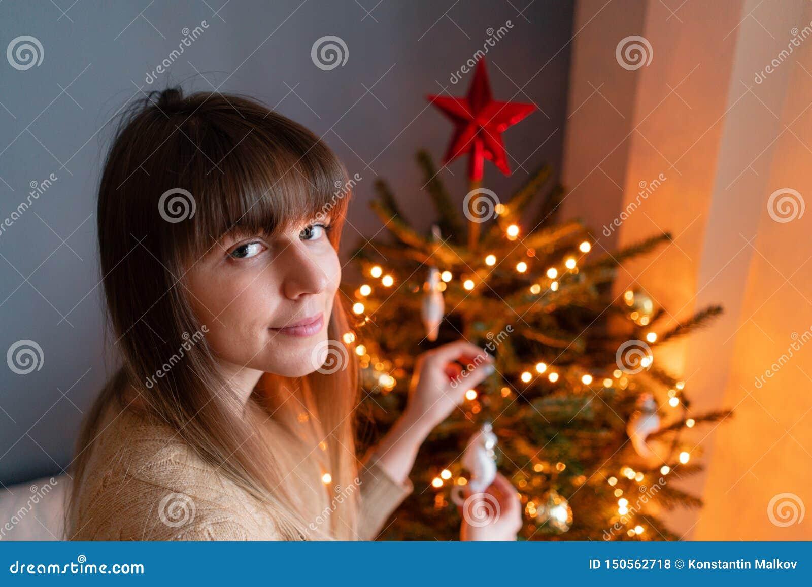 Jeune femme heureuse d?corant l arbre de No?l ? la maison E No?l d or et blanc