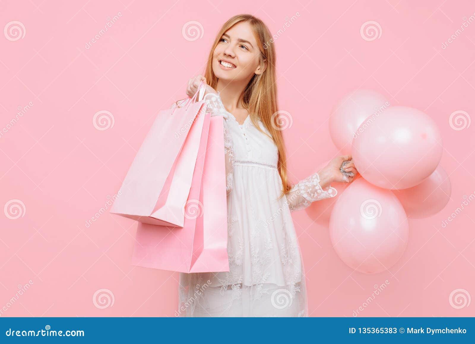 Jeune femme heureuse, dans une robe blanche, avec des sacs dans les mains et des ballons, sur un fond rose Concept d achats