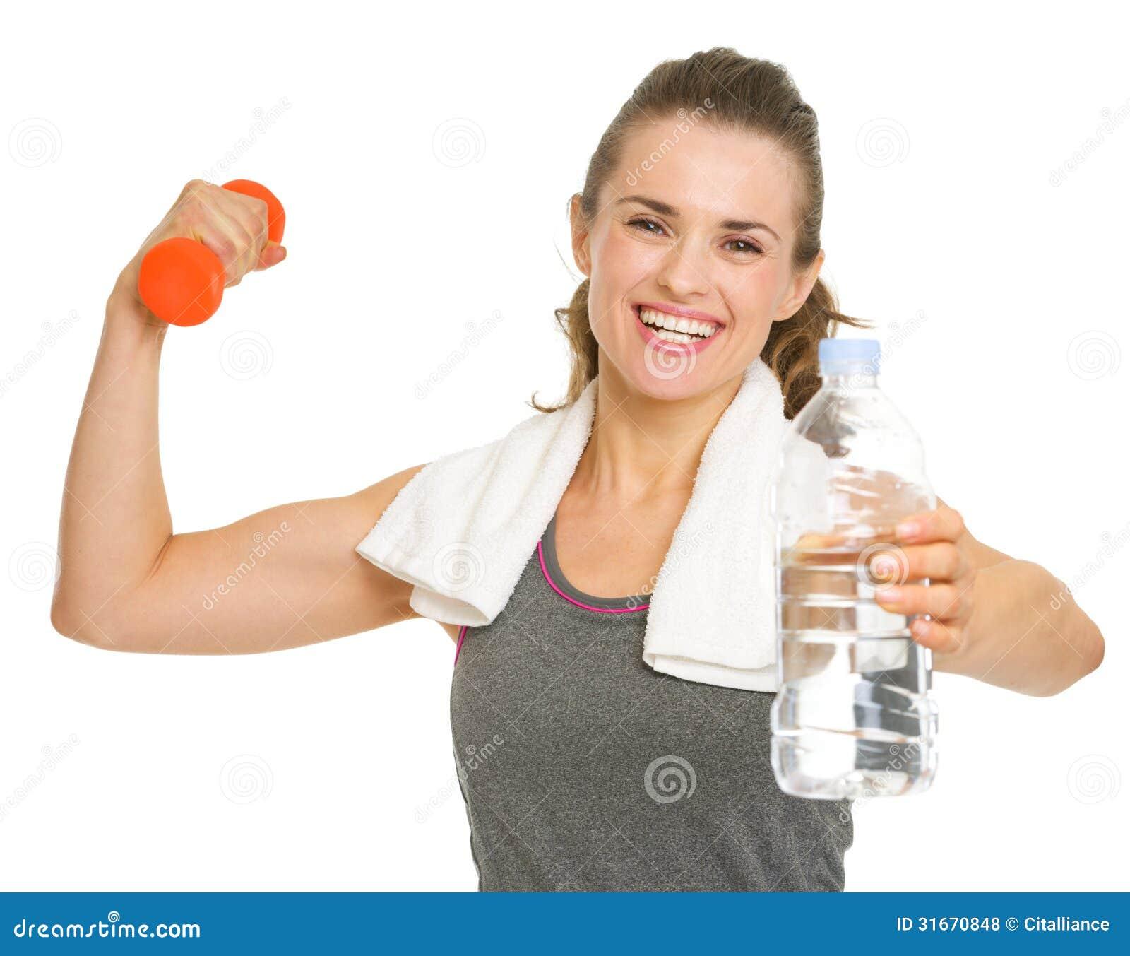 Jeune femme heureuse de forme physique tenant des haltères