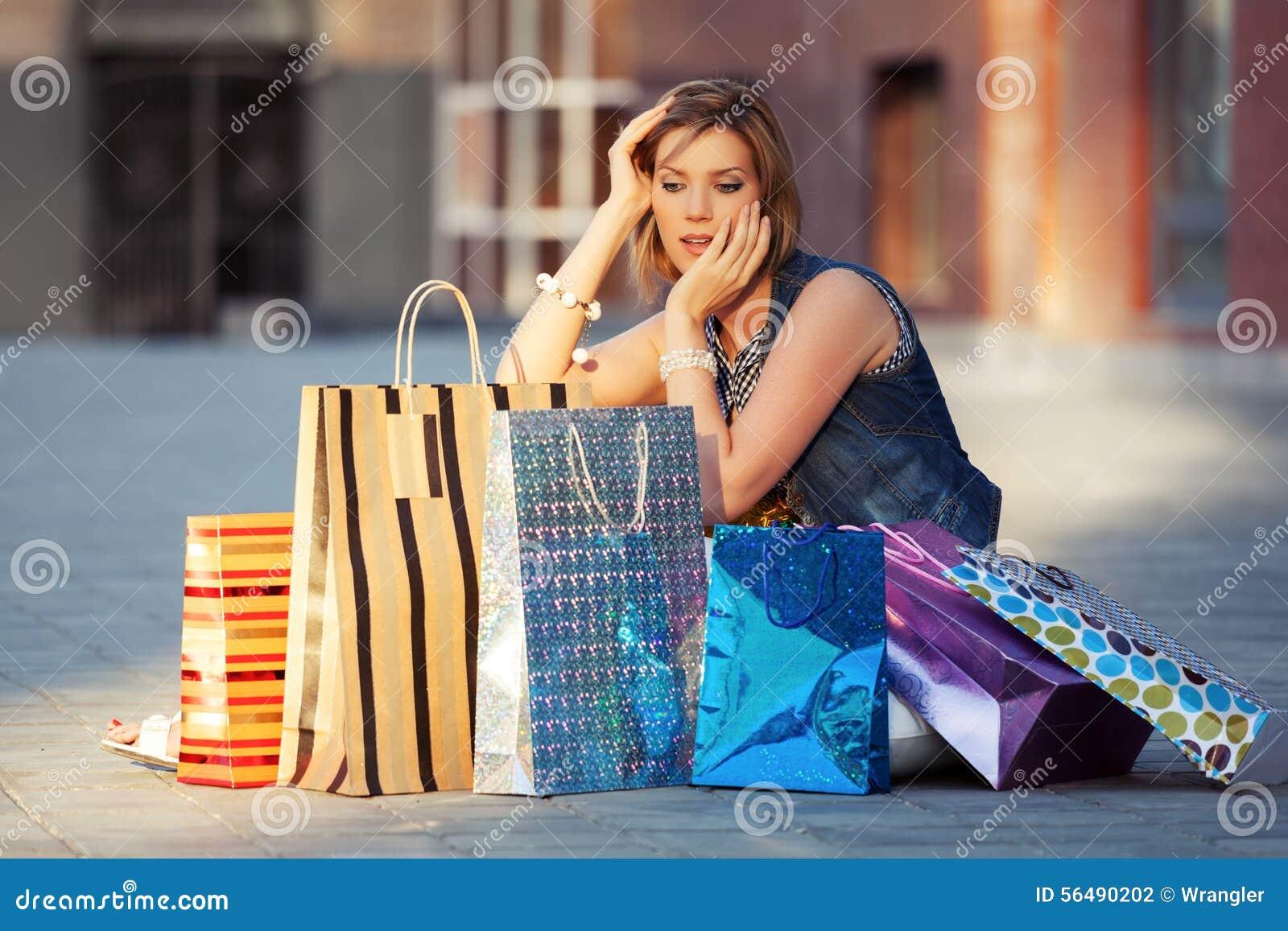 Jeune femme heureuse de mode avec des paniers se reposant sur le trottoir