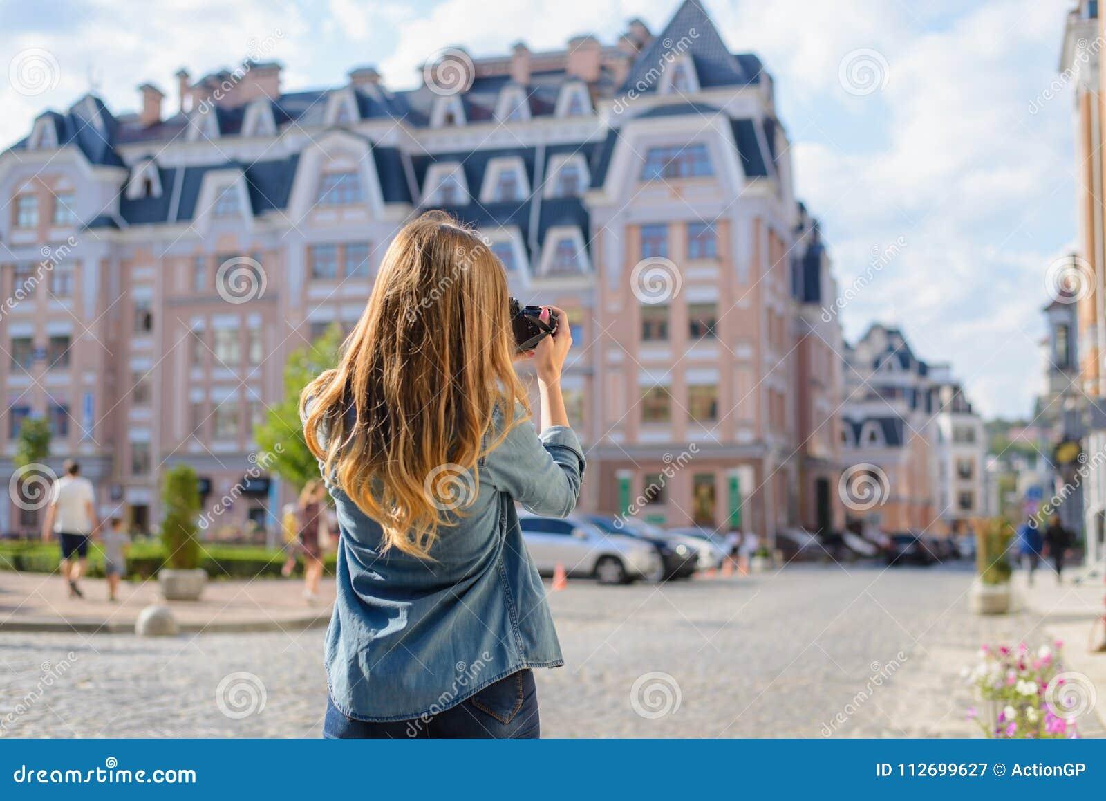 Jeune femme heureuse, enthousiaste, élégante rapportant la photo du point de repère au bel arrière euripean nouveau vieux de vill