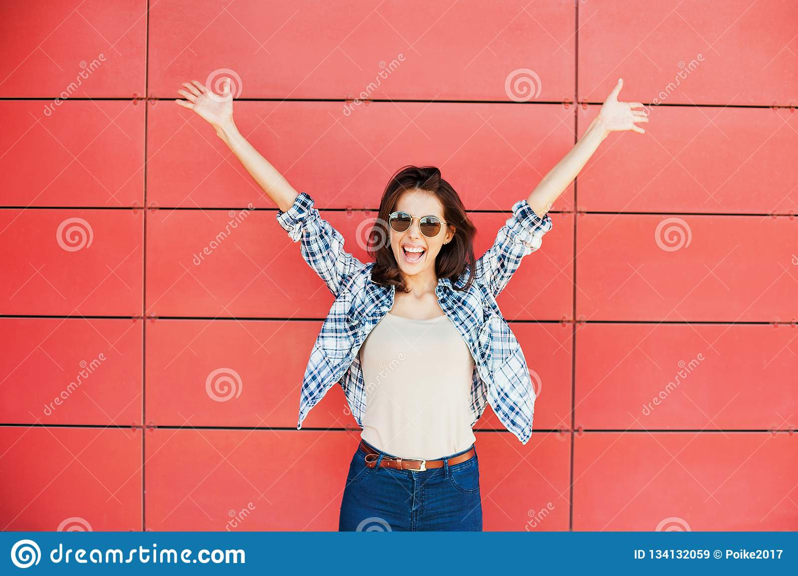 Jeune femme heureuse joyeuse sautant contre le mur rouge Beau portrait enthousiaste de fille