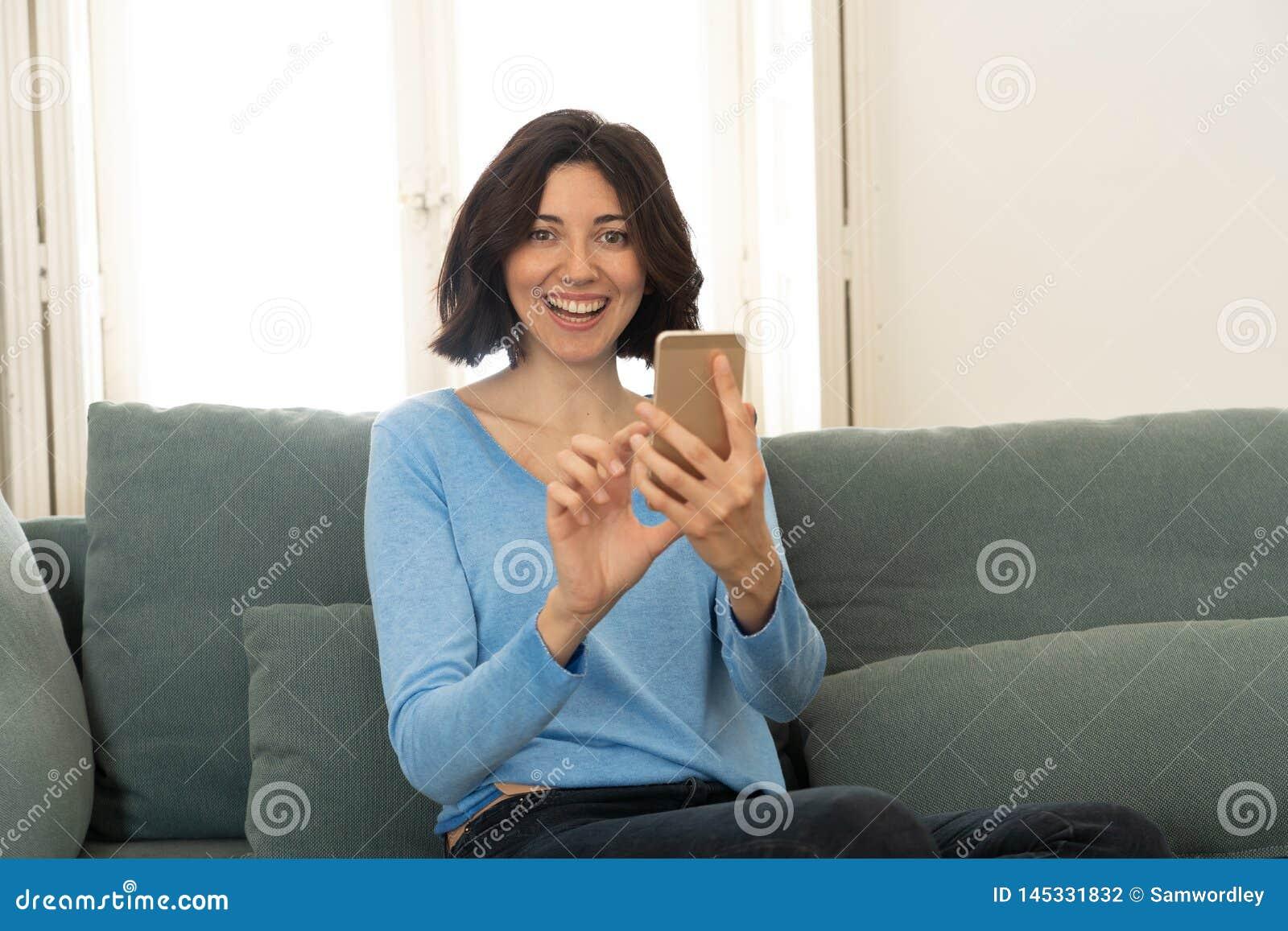 Jeune femme heureuse ? l aide de son t?l?phone intelligent se reposant sur le sofa ? la maison Dans les loisirs et la dépendance