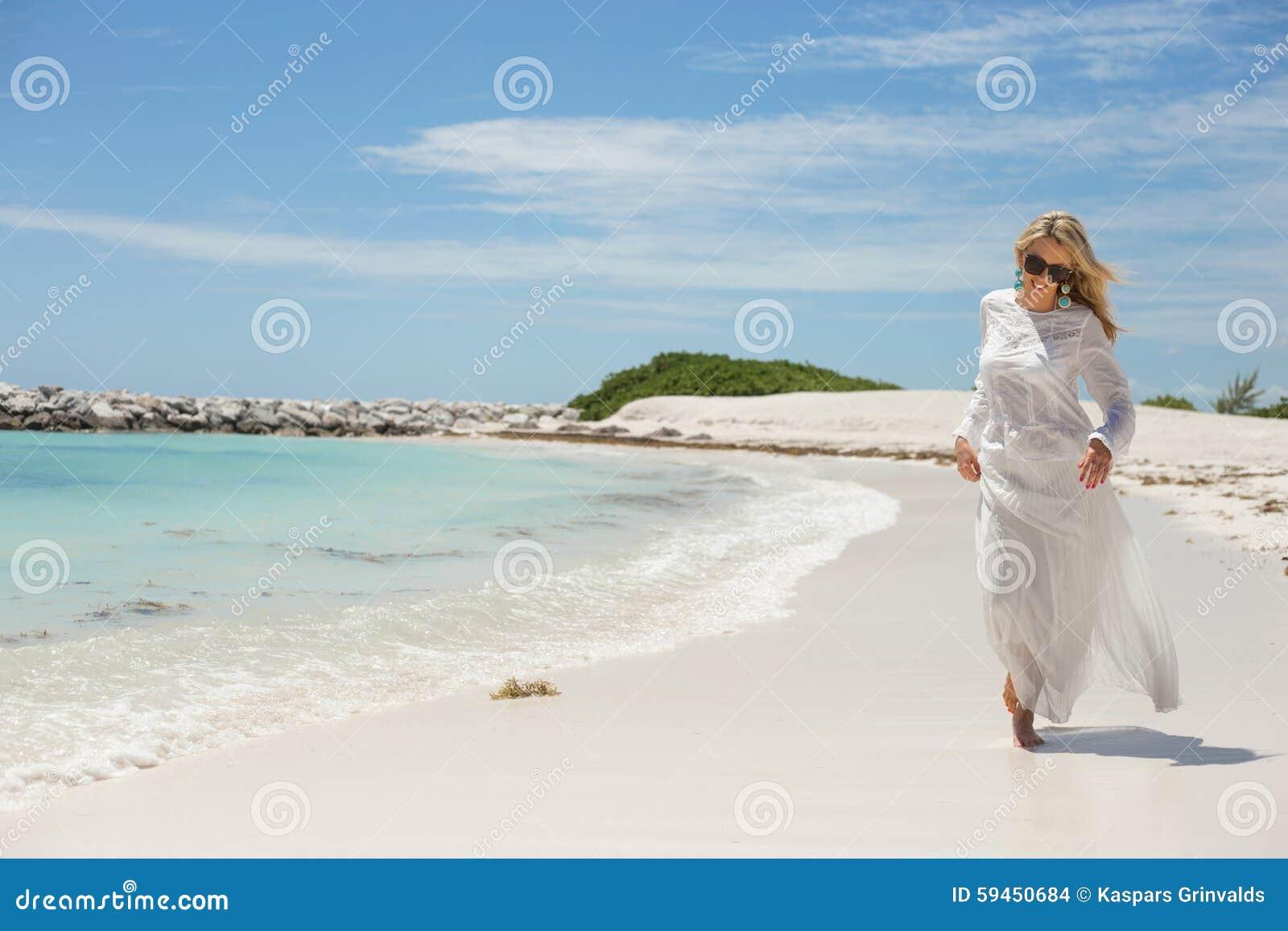 Jeune femme heureuse marchant sur la plage