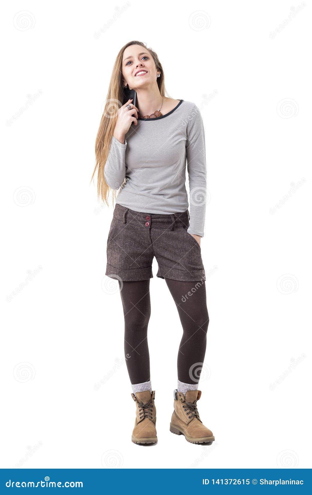 Jeune femme heureuse mise pour inviter la prise faisant une pause et tenant le téléphone portable sous l oreille