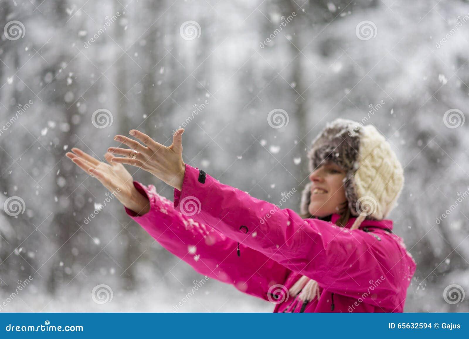 Jeune femme heureuse portant le chapeau chaud et le standi rose lumineux de veste