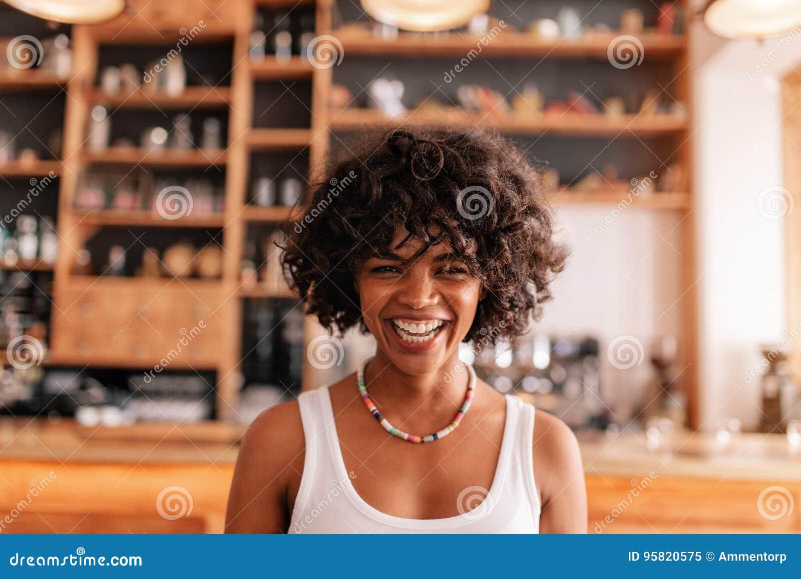 Jeune femme heureuse riant dans un café
