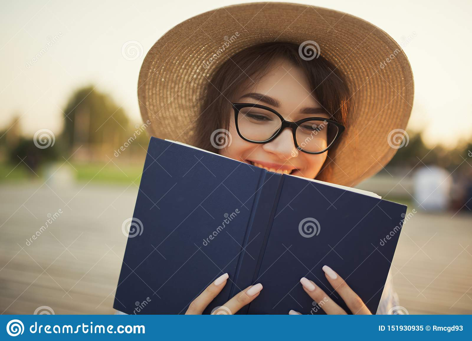 Jeune femme heureuse s asseyant en parc Souriant et tenant un livre dans des ses mains