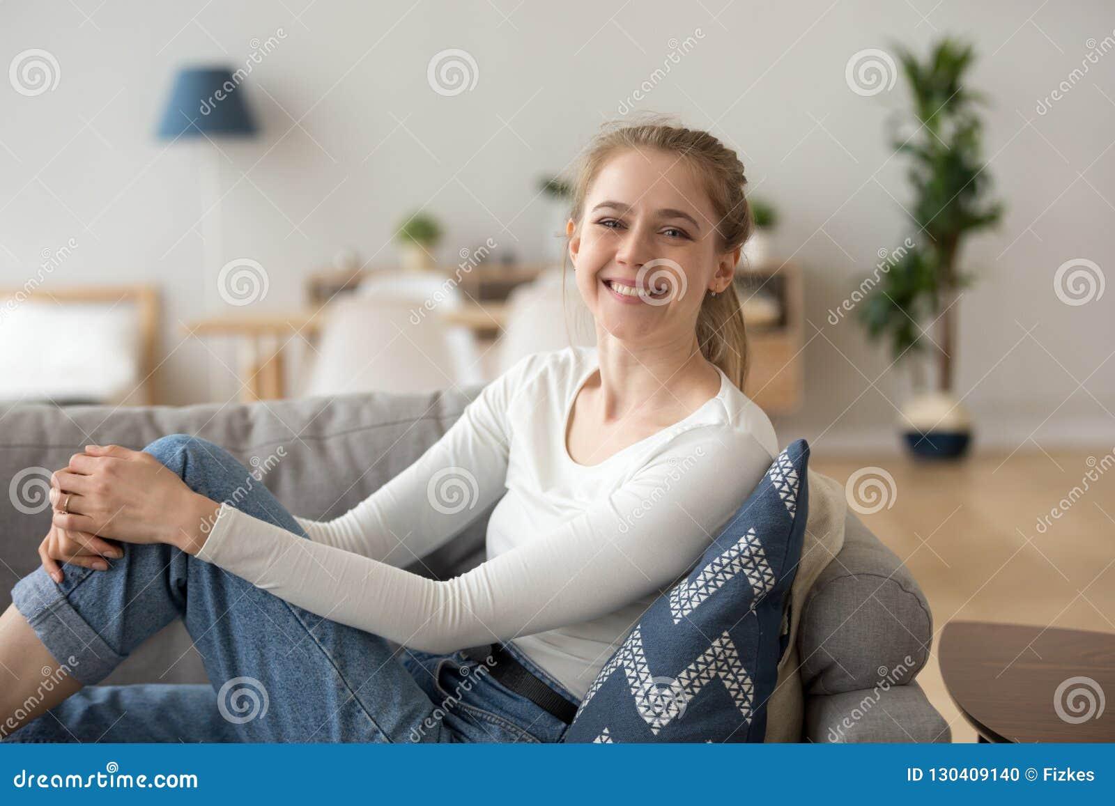 Jeune femme heureuse s asseyant sur le divan à la maison