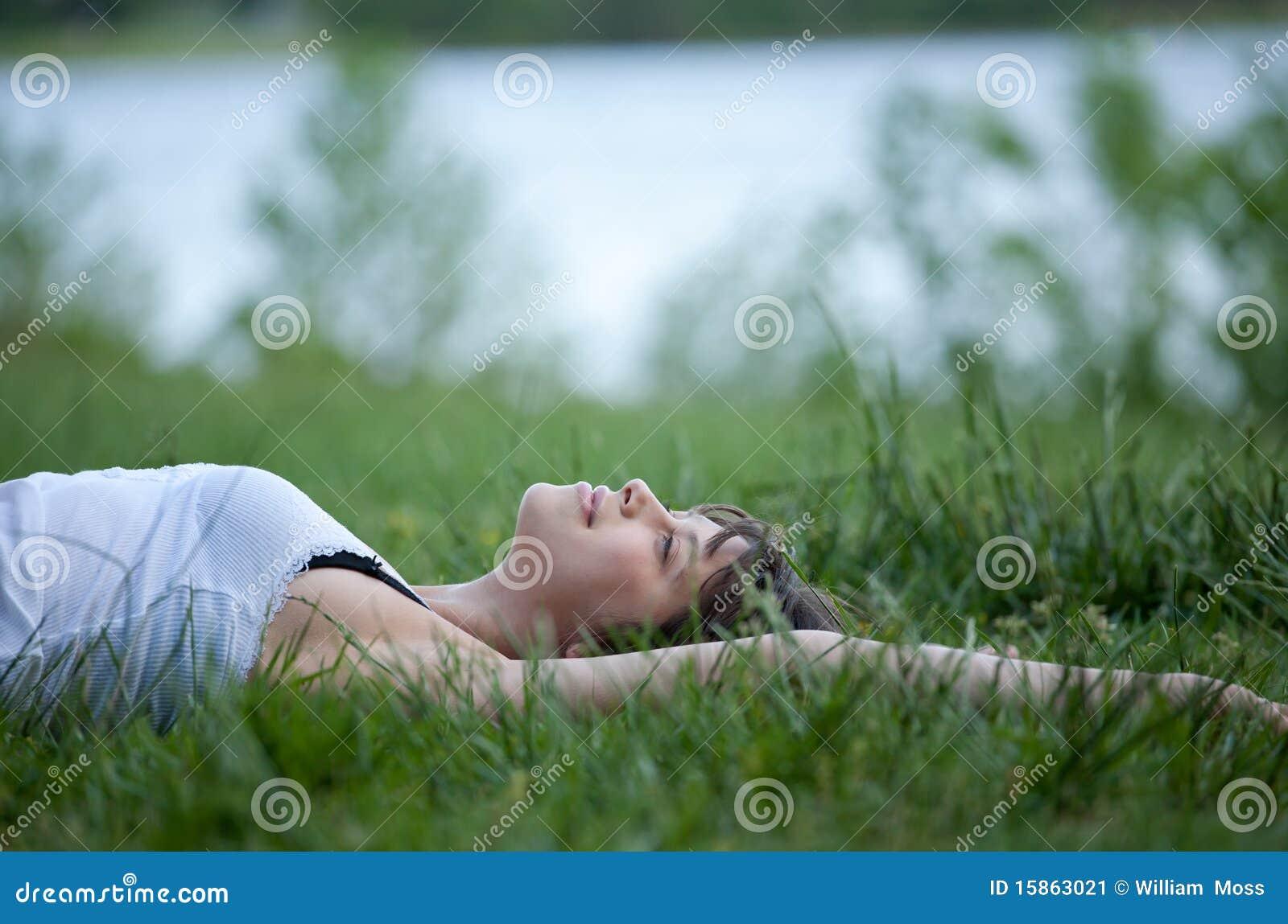 Jeune femme heureux se situant dans le domaine