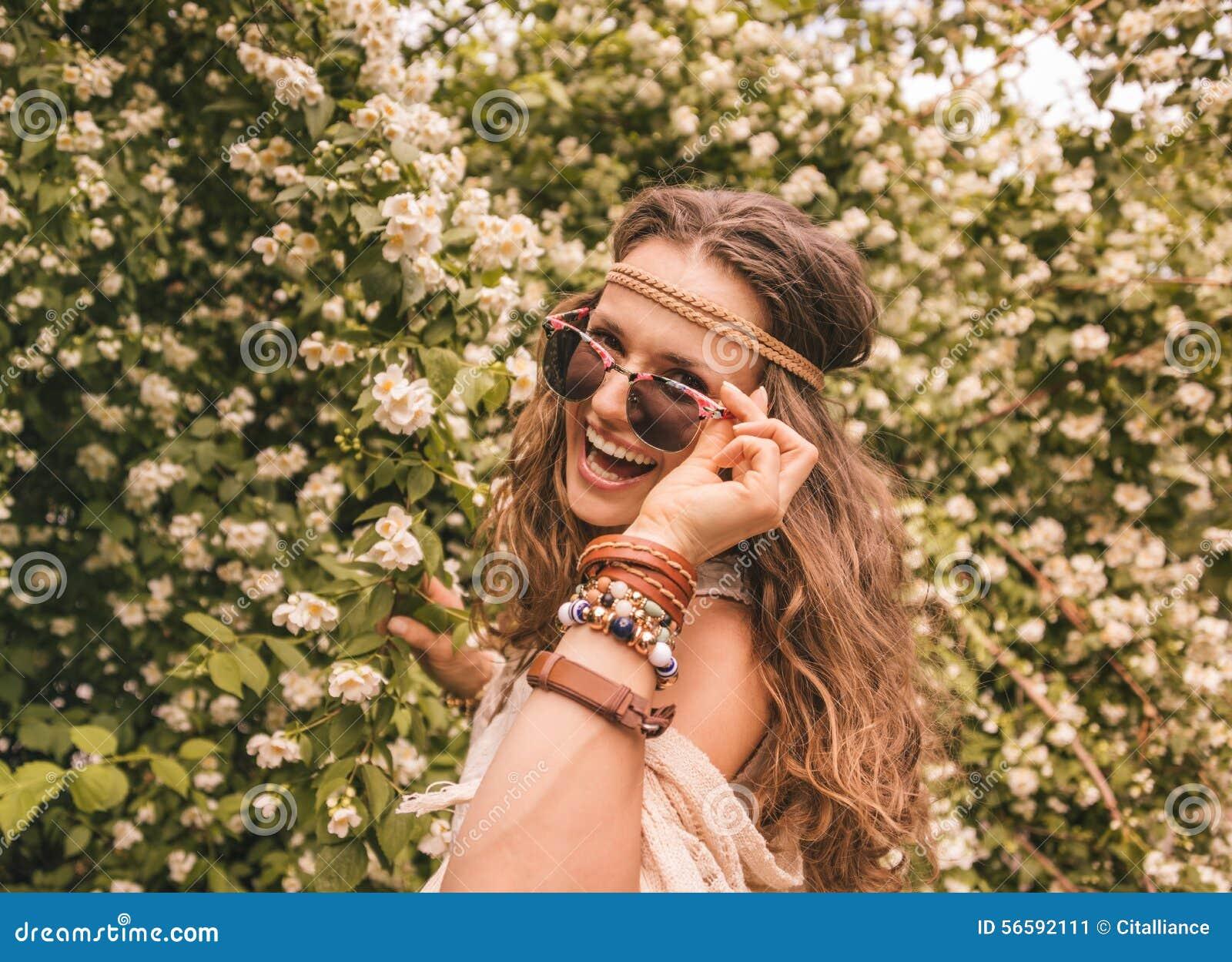 Jeune dame à l air la hippie à cheveux longs dans le châle tricoté et le  chemisier blanc se tenant parmi des fleurs c7724bcf9a79