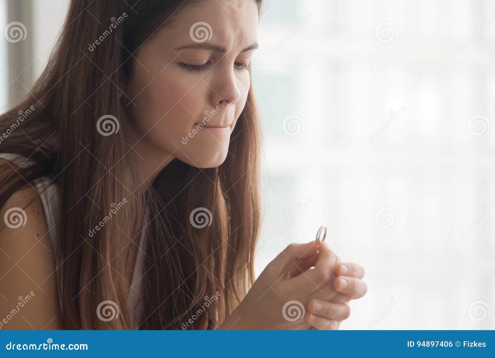 Jeune femme inquiétée regardant sur l anneau d or à disposition