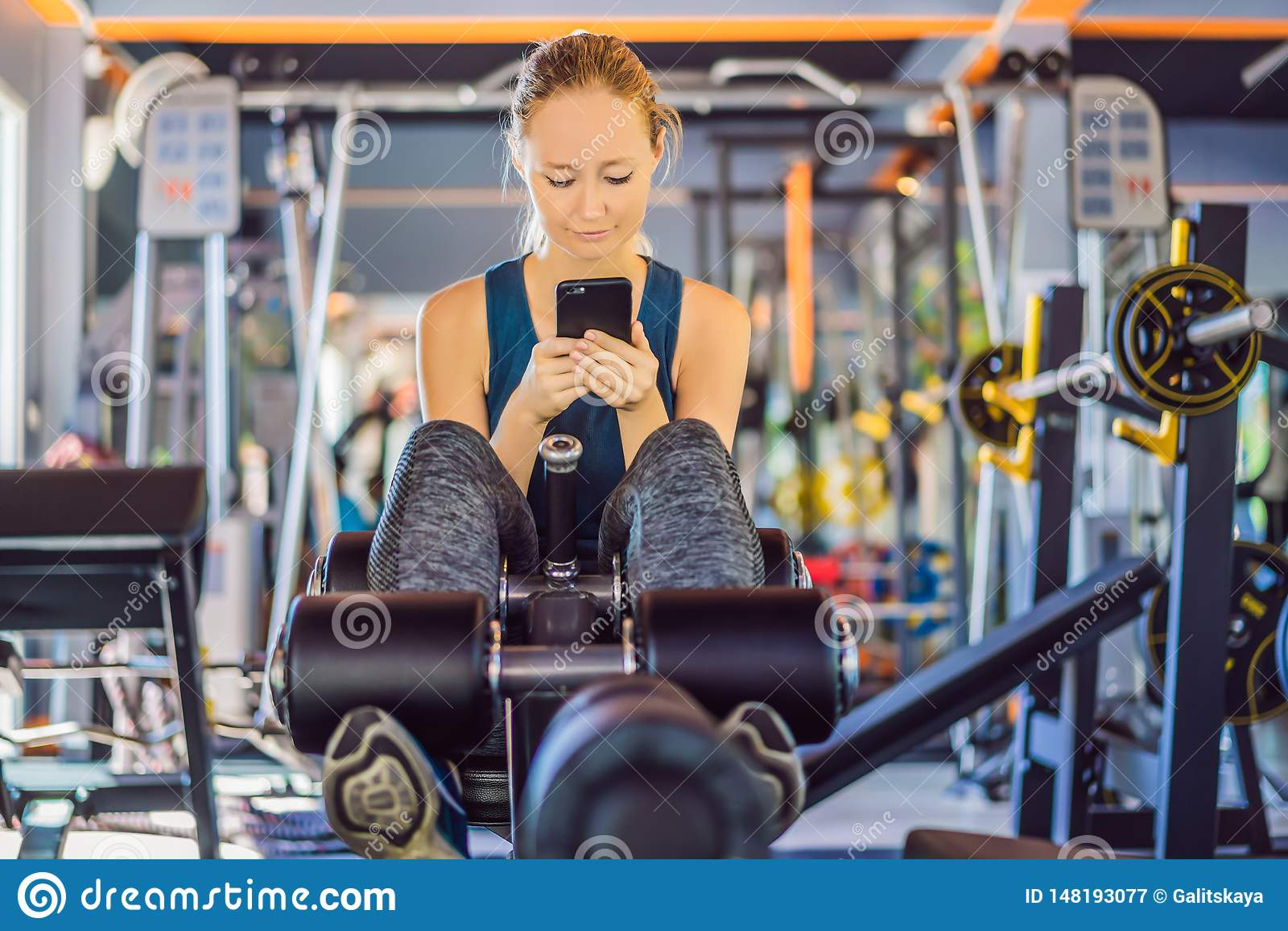 Jeune femme ? l aide du t?l?phone tout en s exer?ant au gymnase Femme s asseyant sur exercer la machine tenant le t?l?phone porta