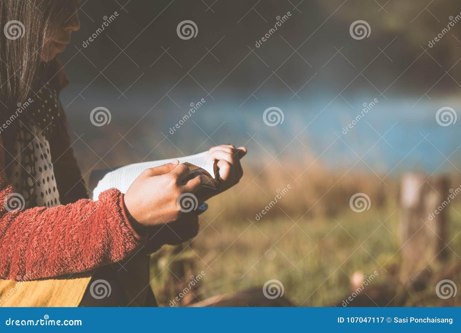 Jeune femme lisant un livre en parc naturel avec la fraîcheur