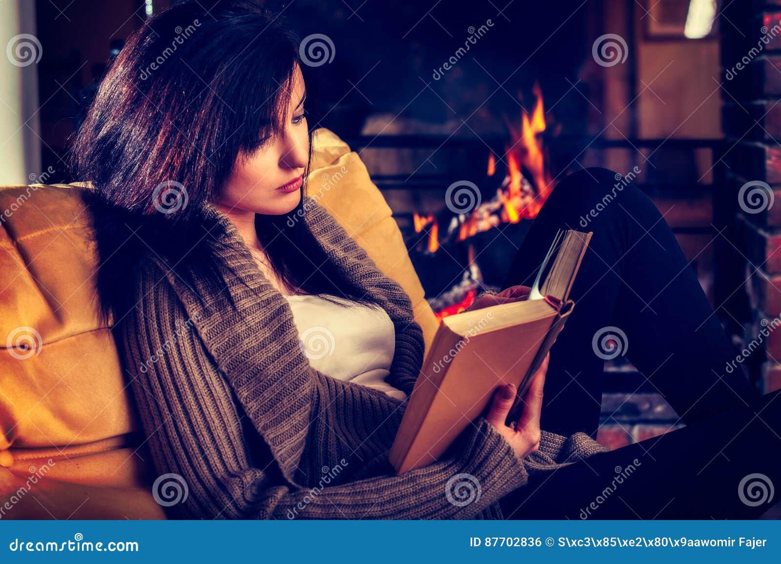 Jeune femme lisant un livre par la cheminée