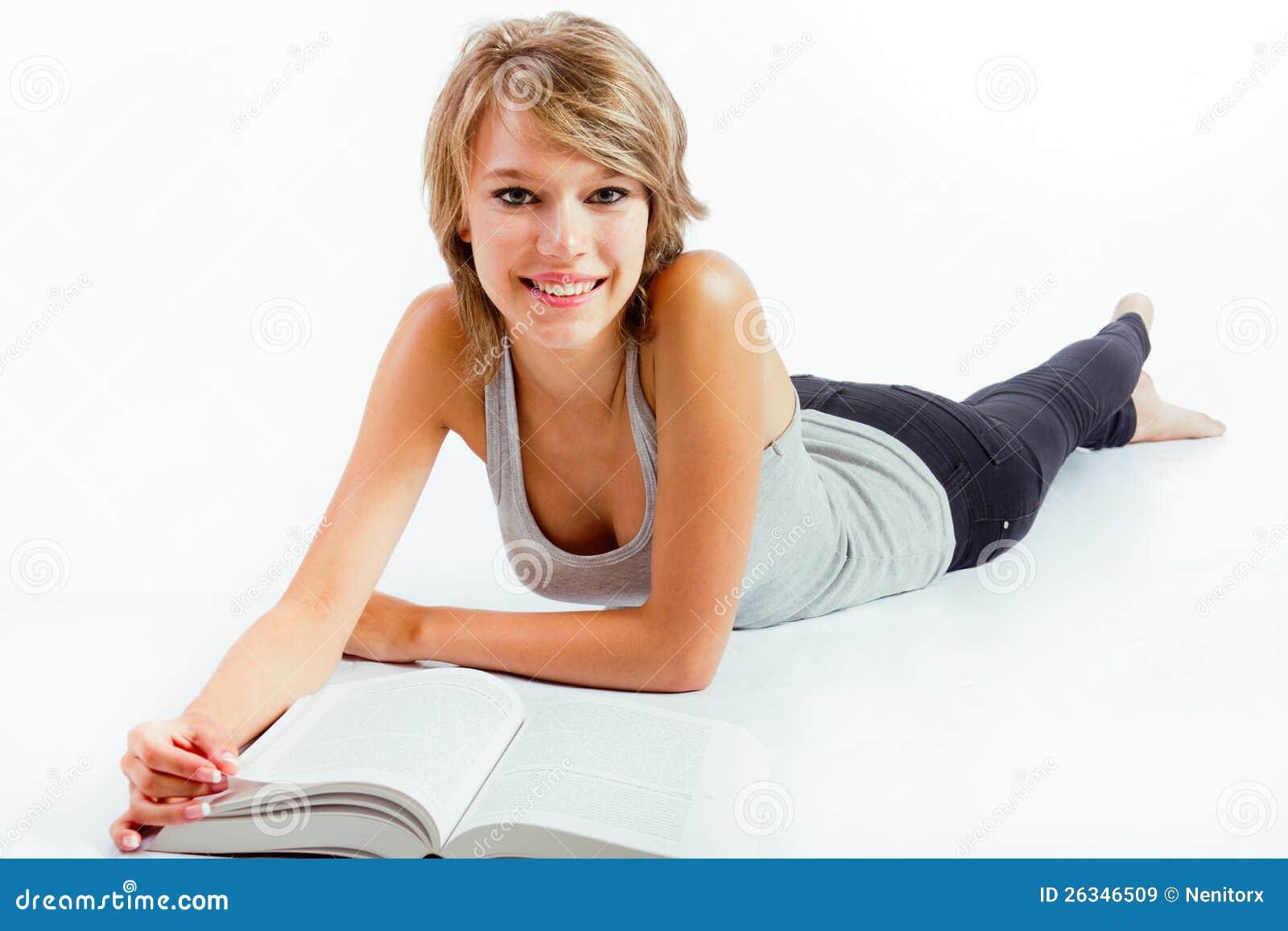 Jeune femme lisant un livre sur le plancher