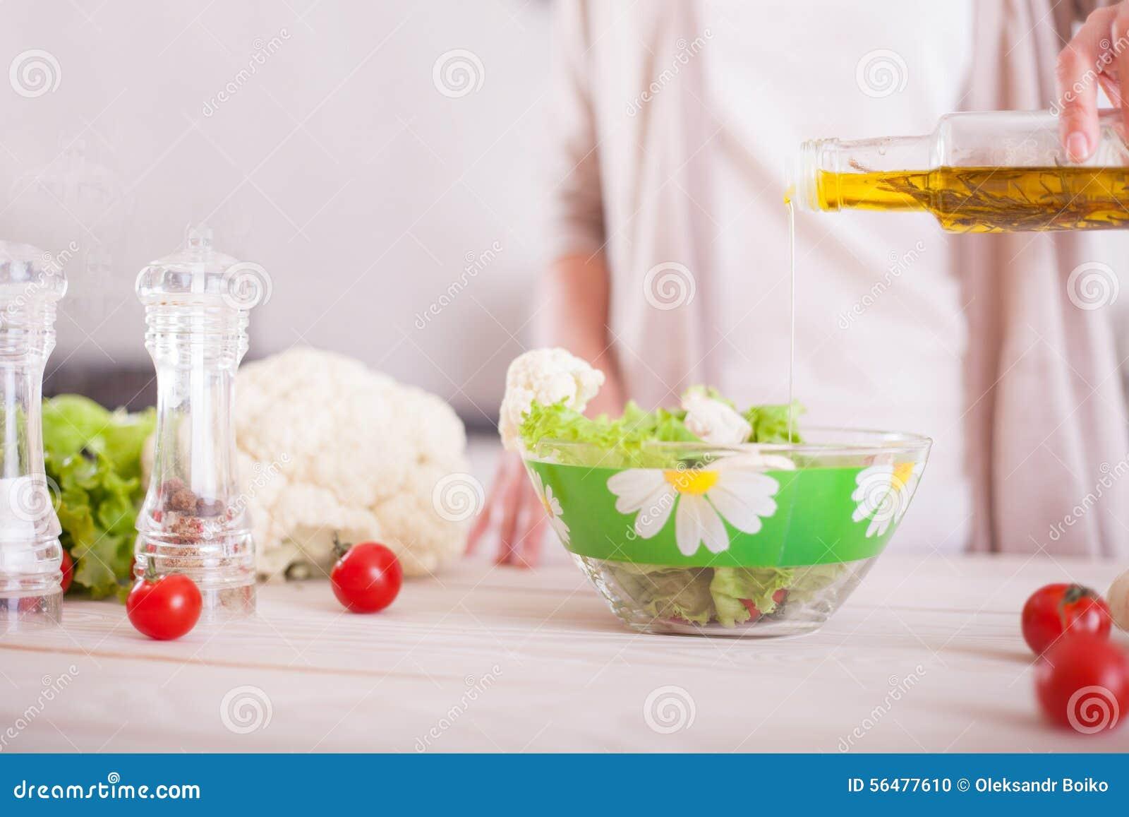 Jeune femme mélangeant la salade fraîche