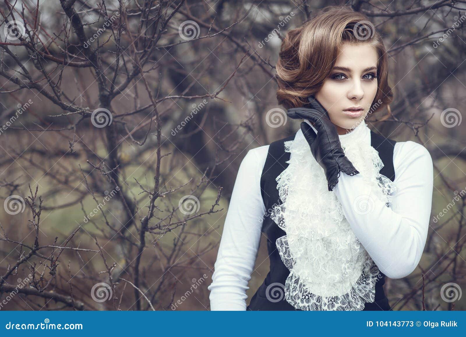 Jeune femme magnifique avec la coiffure victorienne élégante tenant sa main dans le gant en cuir à sa joue