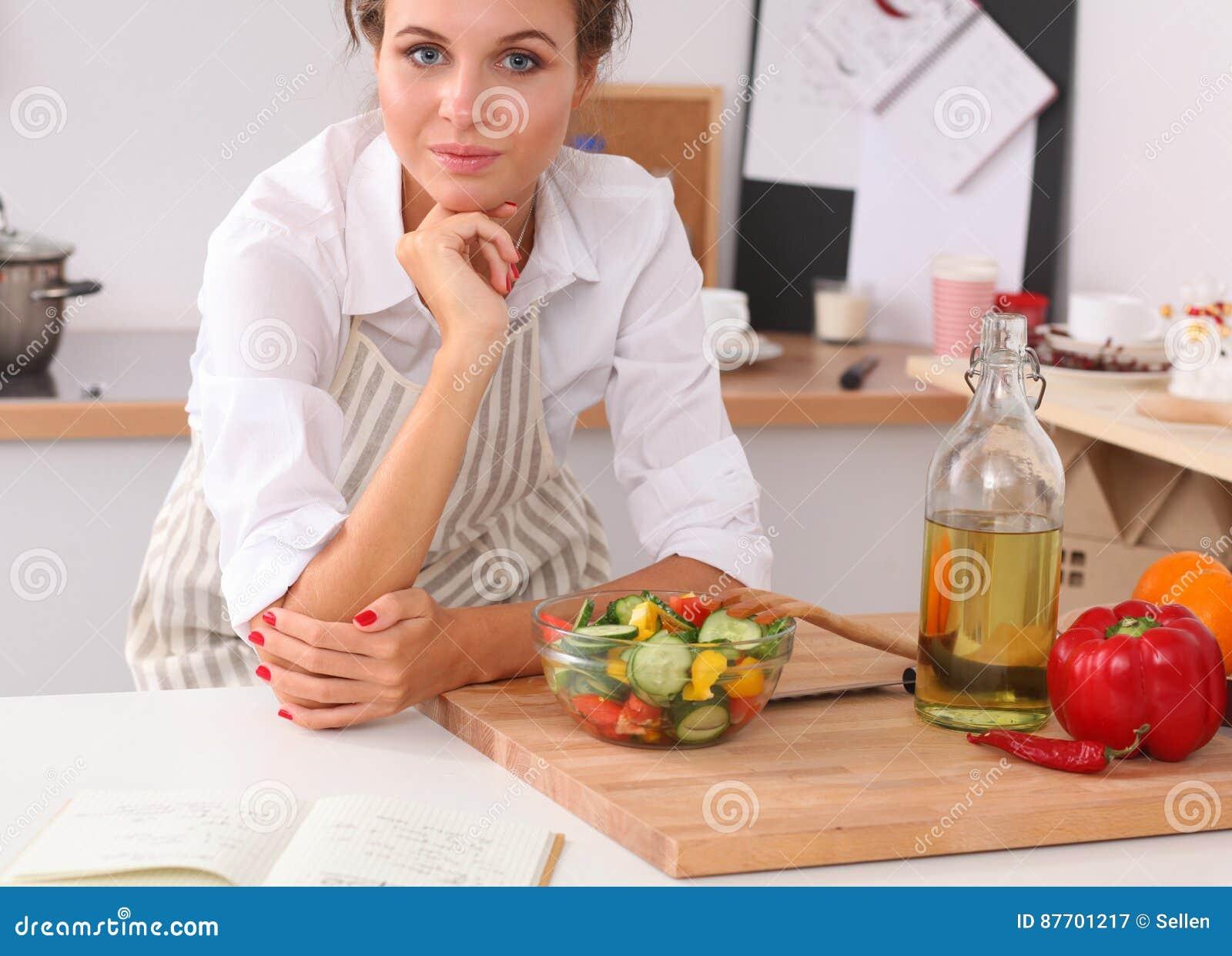Jeune femme mangeant de la salade fraîche dans la cuisine moderne