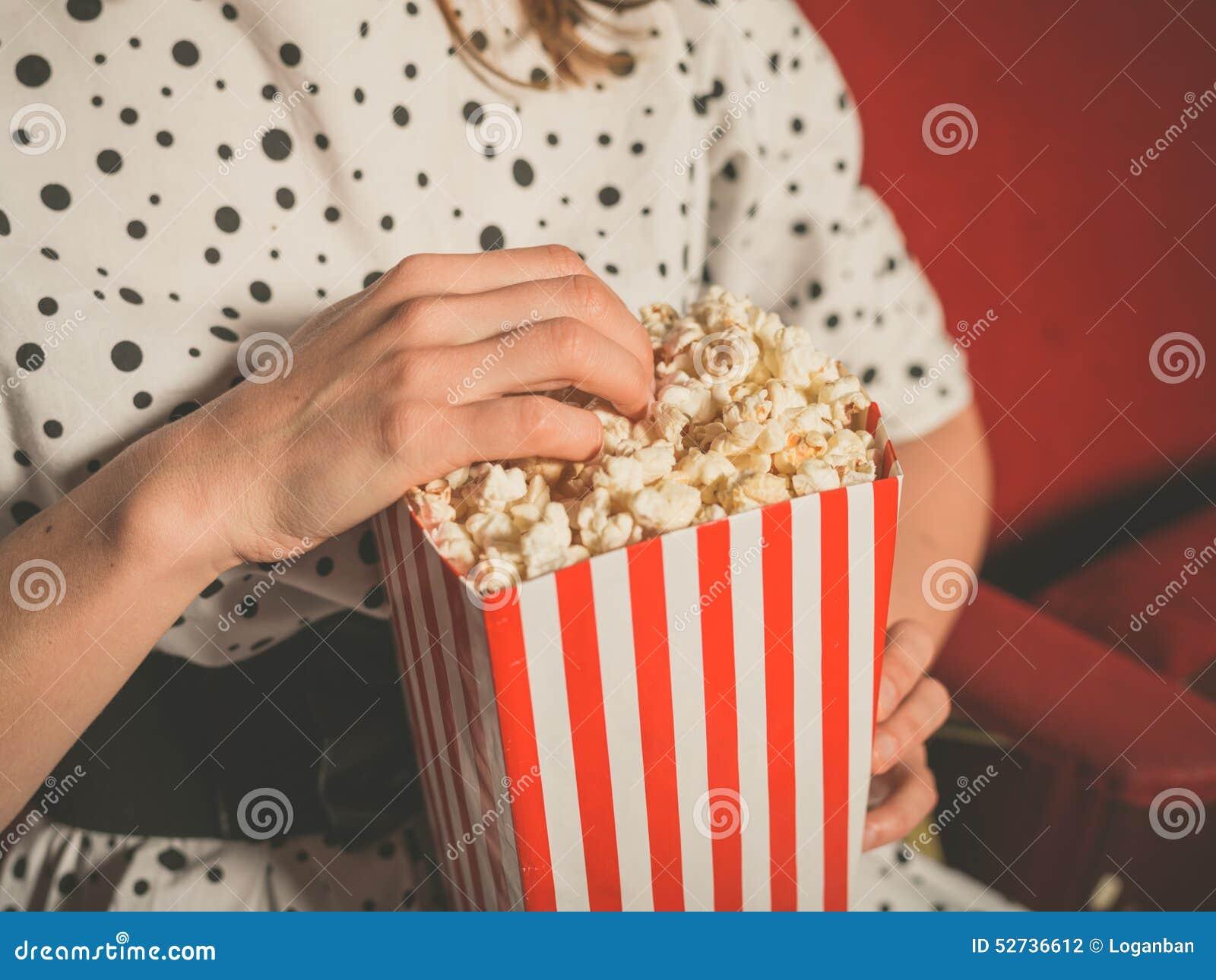 Jeune femme mangeant du maïs éclaté dans la salle de cinéma