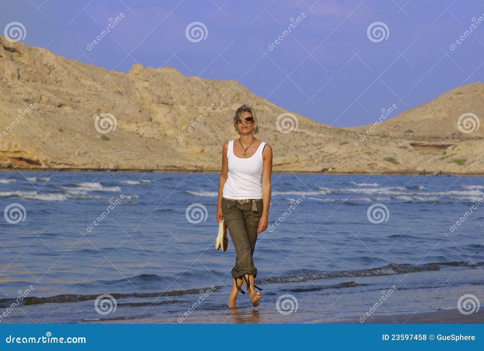 Jeune femme marchant à la plage