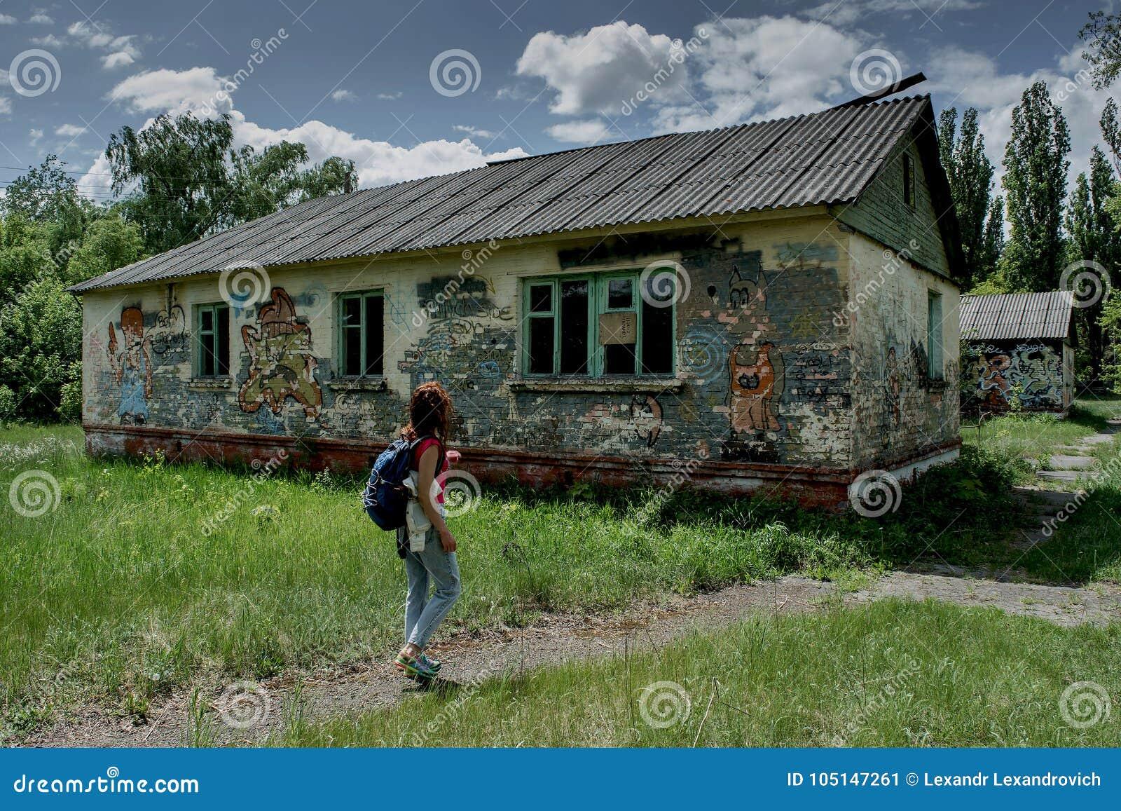 Jeune femme marchant sur la route près de la maison abandonnée rampante