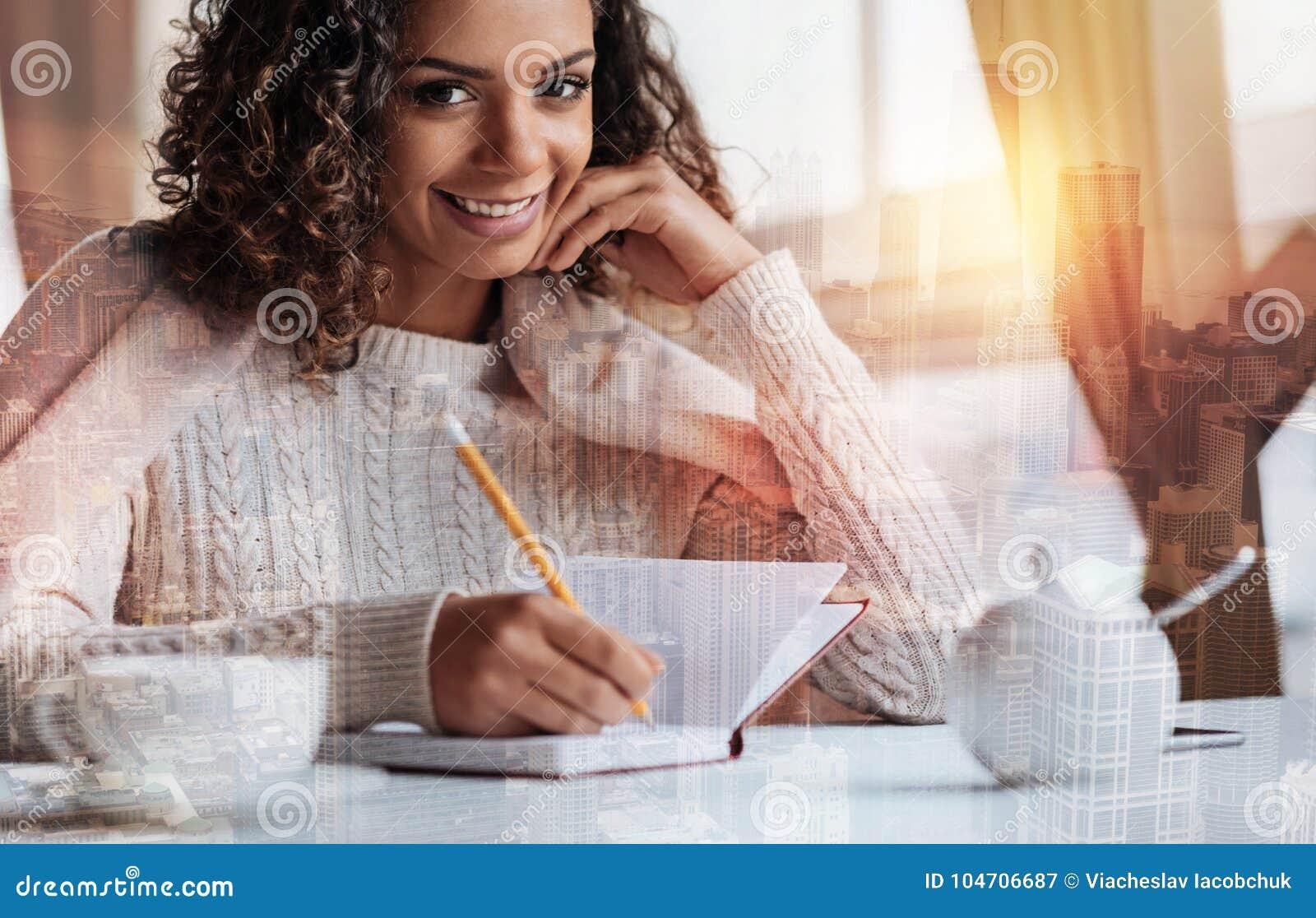 Jeune femme mignonne souriant tout en écrivant l information importante dans son carnet