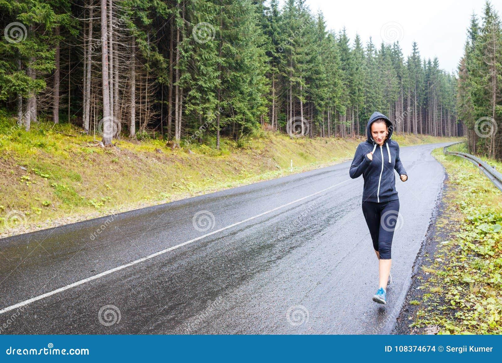 Jeune femme mince pulsant sur la route de montagne