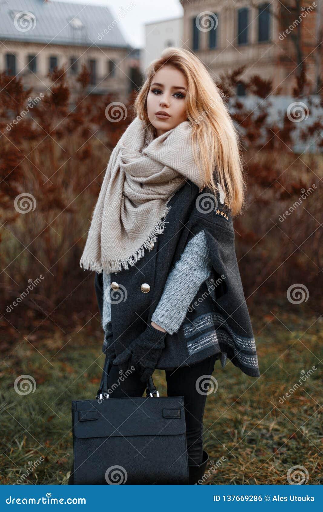 Jeune femme moderne élégante dans un chandail tricoté gris dans un manteau noir avec une écharpe dans des jeans noirs avec un sac