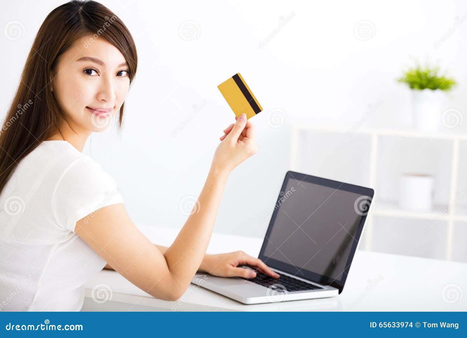 Jeune femme montrant la carte de crédit et l ordinateur portable