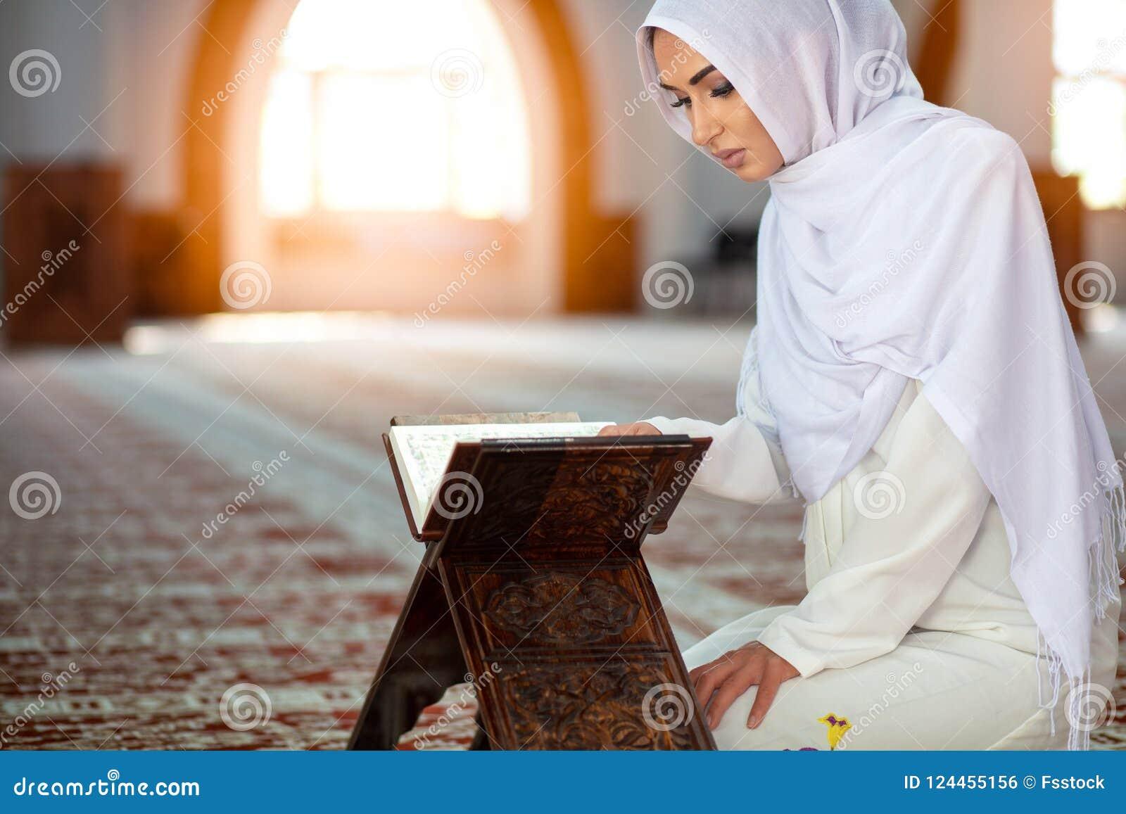 Jeune femme musulmane priant dans la mosquée avec le quran