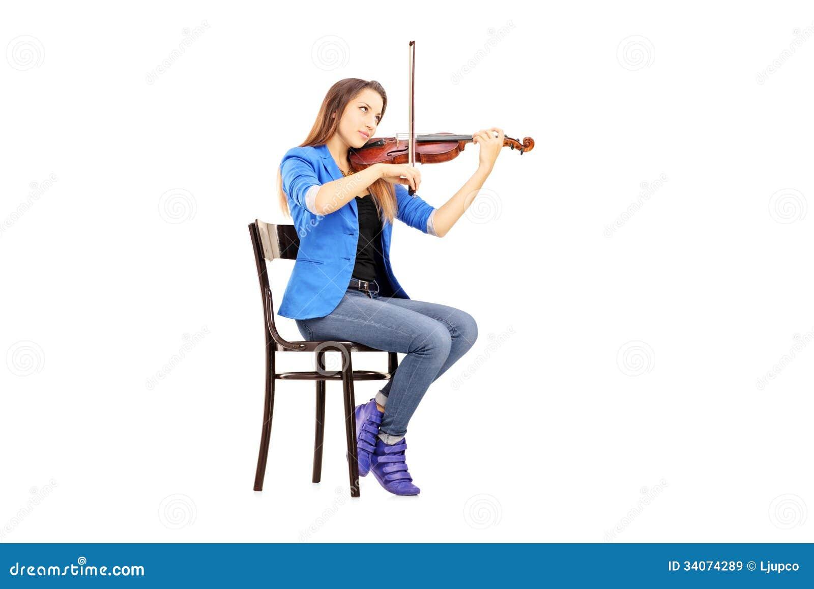 jeune femme occasionnelle assise sur une chaise en bois jouant le violon image stock image du. Black Bedroom Furniture Sets. Home Design Ideas