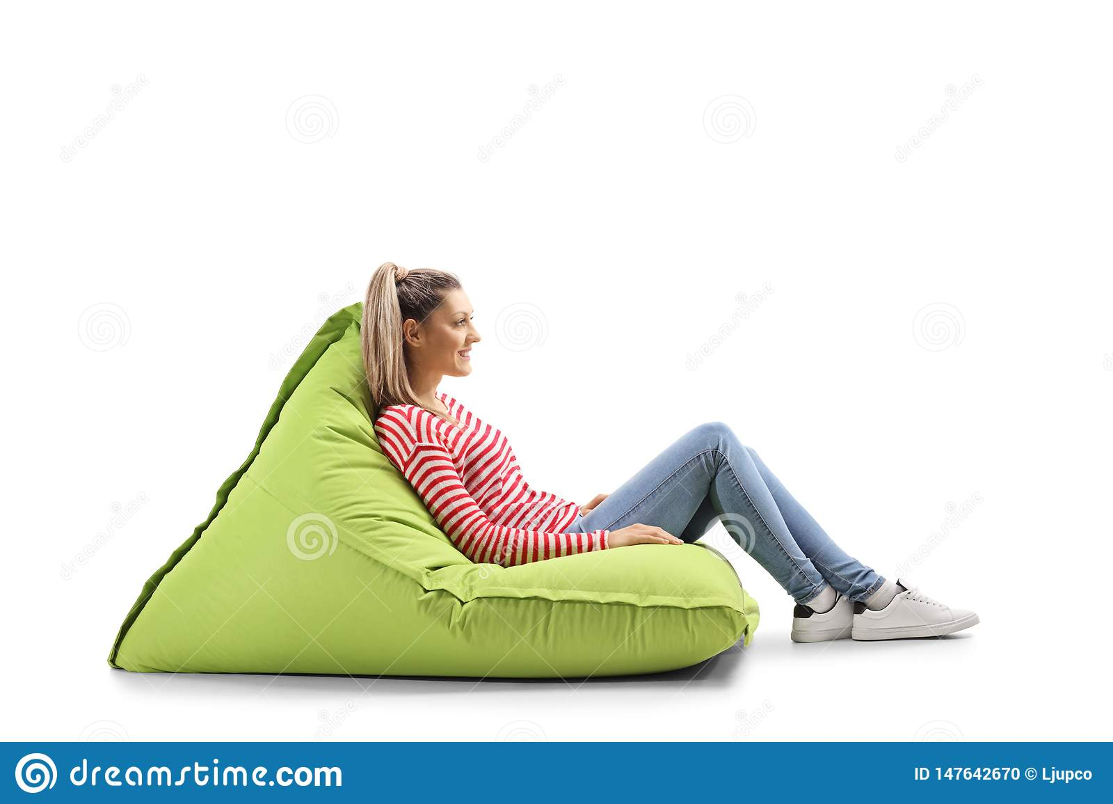 Jeune femme occasionnelle blonde s asseyant sur un fauteuil poire vert
