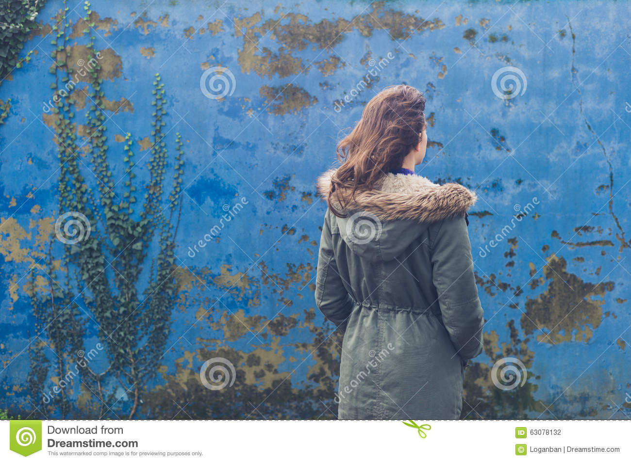 Download Jeune Femme Par Le Mur Bleu Le Jour Venteux Photo stock - Image du outdoors, mode: 63078132