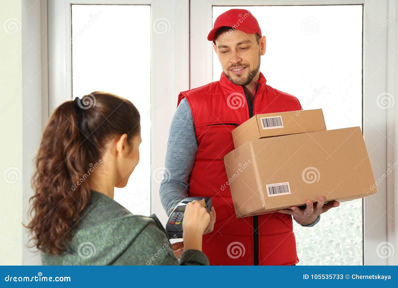 Jeune femme payant des colis reçus du messager