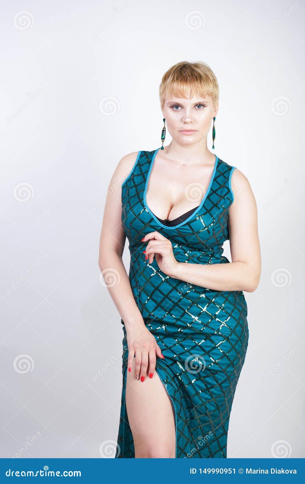 Jeune femme plus avec du charme de taille avec les cheveux blonds courts habillés dans une longue robe luxueuse de vert de soirée