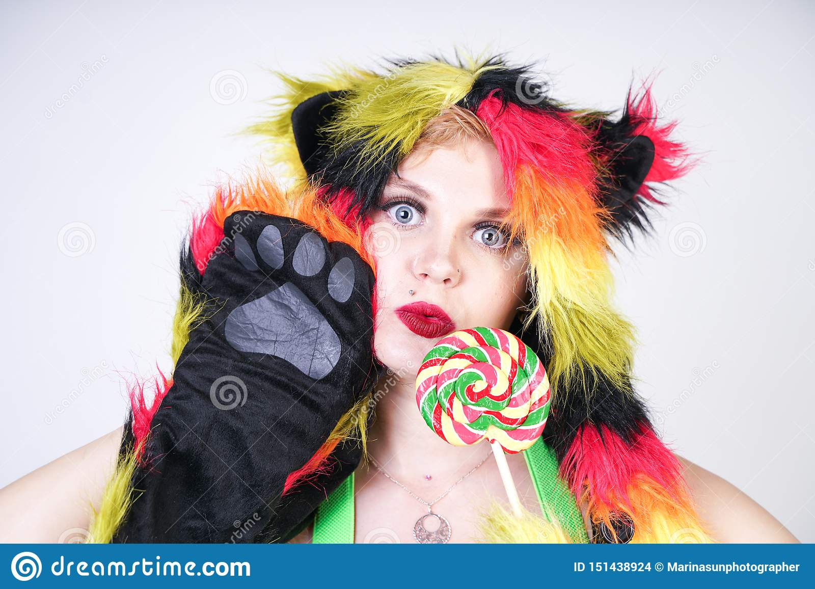 Jeune femme plus de charme de taille dans le chapeau de fourrure fait de fibres multicolores avec des oreilles et des pattes de c