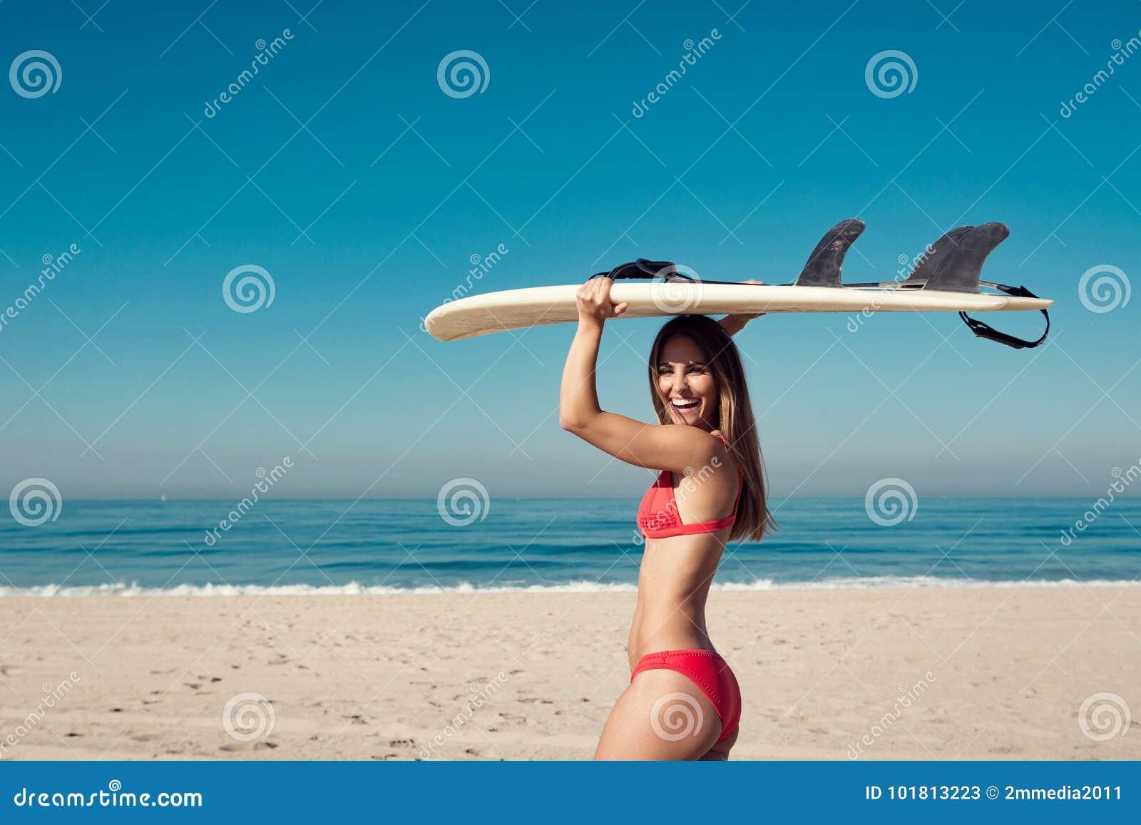 Jeune femme portant une planche de surf à la plage