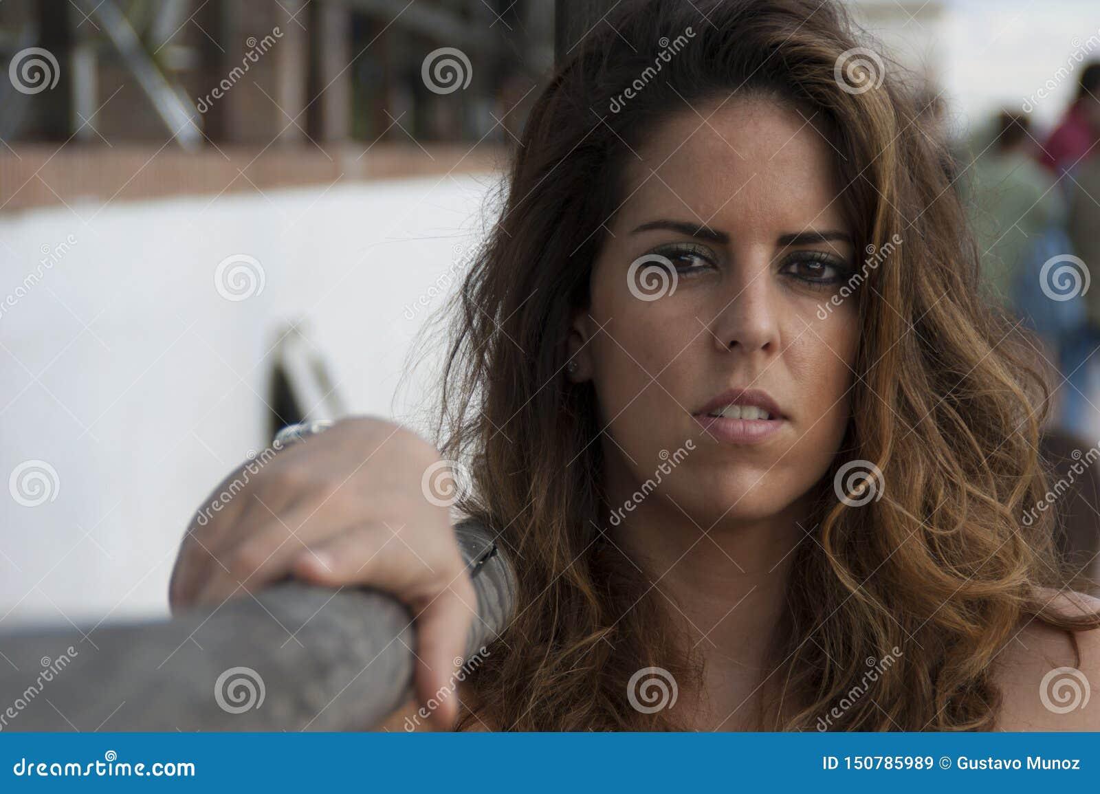 Jeune femme posant regardant la caméra se reposant à côté d une balustrade en bois