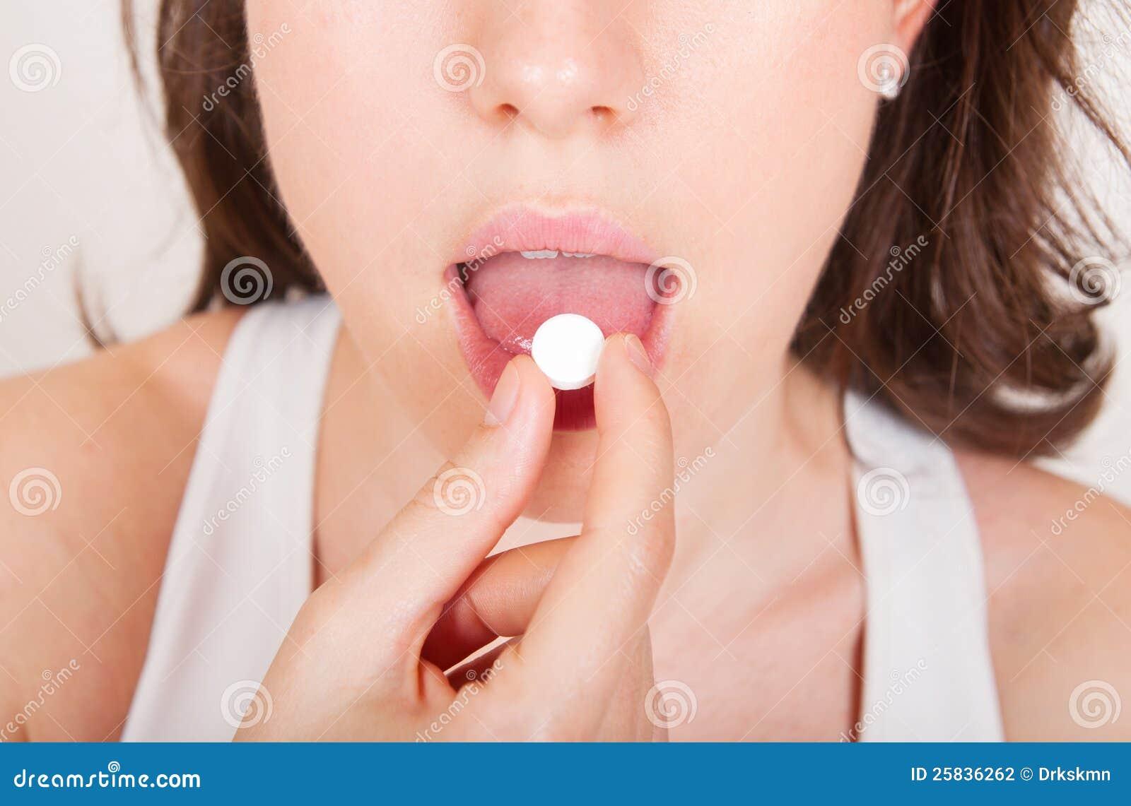 Jeune femme prenant des pillules