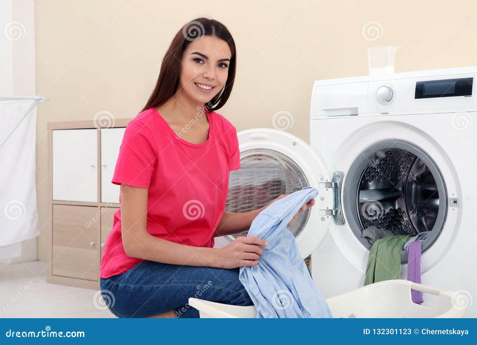Jeune femme prenant la blanchisserie hors de la machine à laver