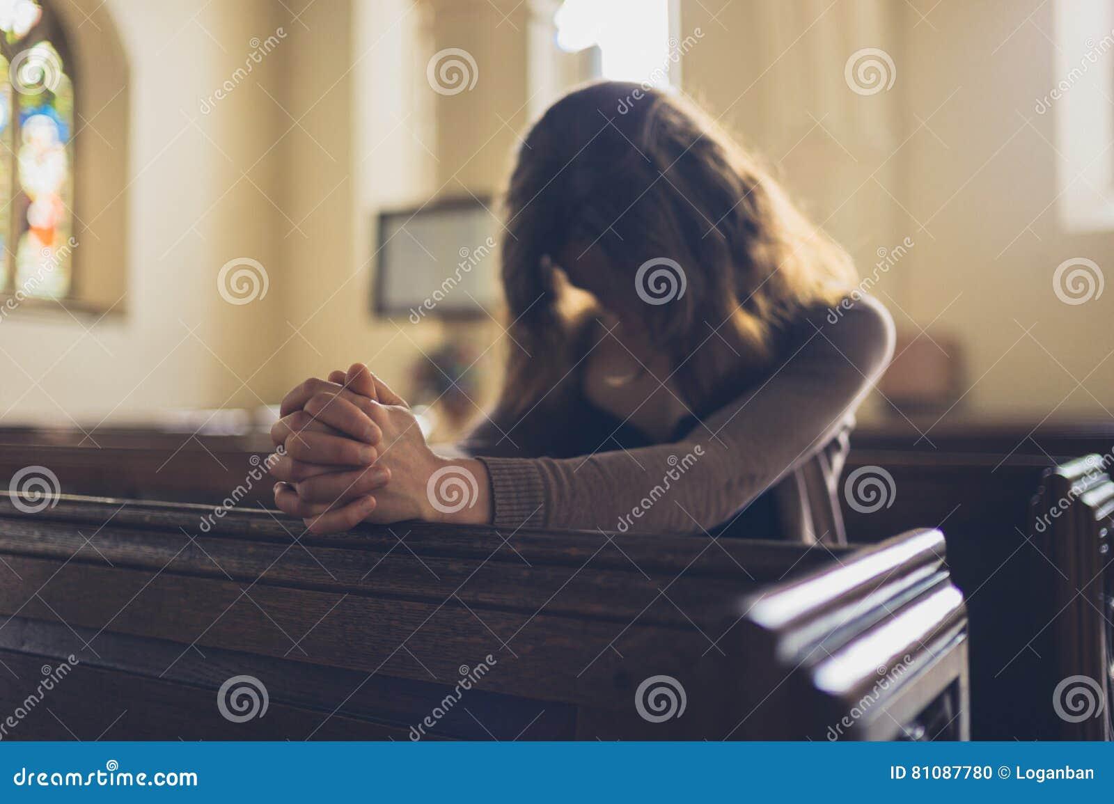 Jeune femme priant dans l église